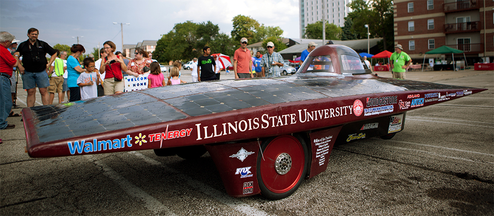 A crowd admires a solar car made by Illinois State students.