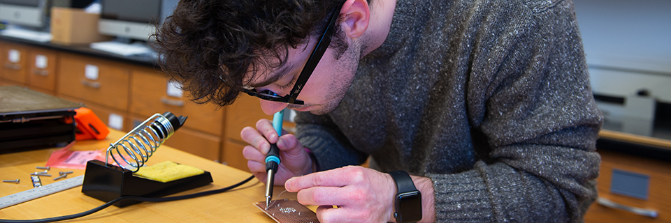 Student soldering wires onto an electrical board.